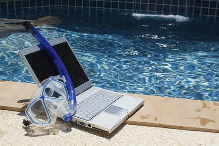 Diving : Laptop and diving mask by the pool side