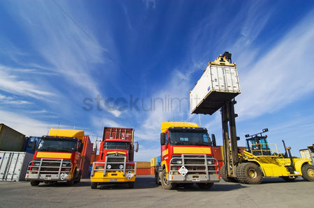 Transportation : Lift truck loading shipping containers onto trucks