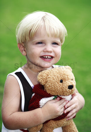 School children : Little boy hugging a toy bear