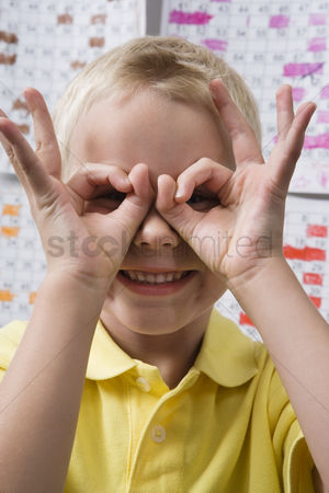 School children : Little boy making binoculars with his hands