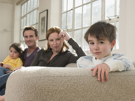 Offspring : Little boy on sofa with family