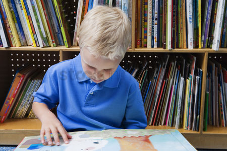 Schoolkids : Little boy reading a picture book