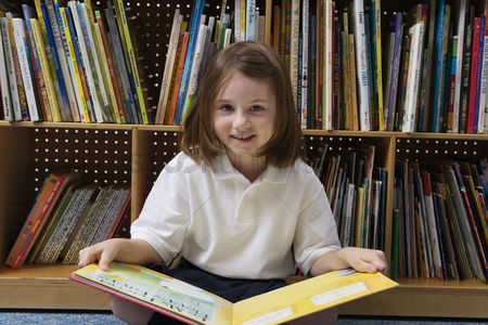 School : Little girl reading in the library