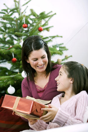 Adulthood : Little girl receiving a christmas present from her mother