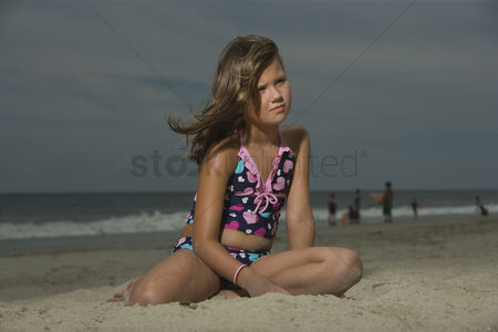 Wondering : Little girl sitting on a beach