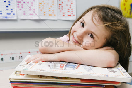 School children : Little girl with a stack of books