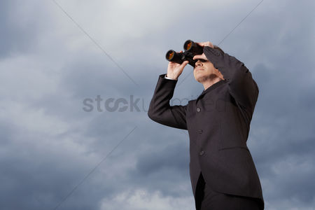 Jacket : Low angle view of businessman looking through binoculars against stormy sky
