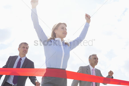 Celebrating : Low angle view of businesswoman crossing finishing line with colleagues in background