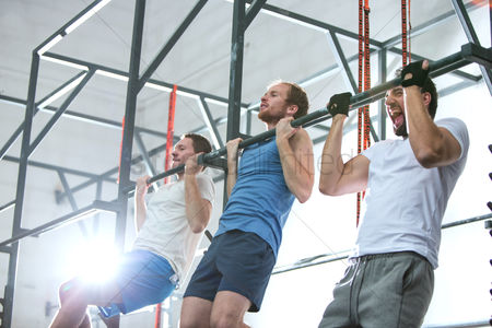 20 24 years : Low angle view of dedicated men doing chin-ups in crossfit gym