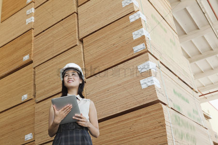 Pile : Low angle view of female industrial worker holding tablet pc with stacked wooden planks in background