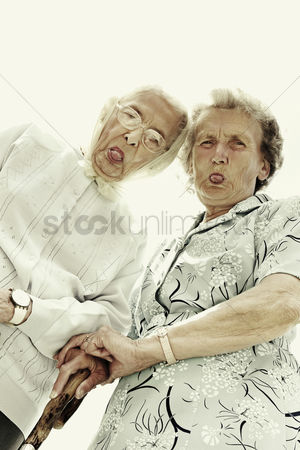 Strong : Low angle view of two old women showing their tongues at the camera