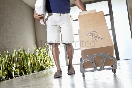 Pushing : Low section of a man walking with packages on handtruck