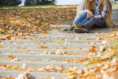 Steps : Low section of couple sitting on steps in park during autumn