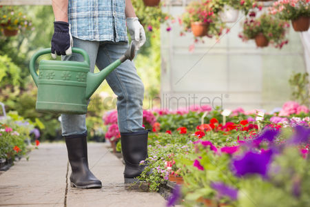 40 44 years : Low section of man holding watering can at greenhouse