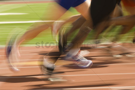 Sports : Low section of runners running on a track