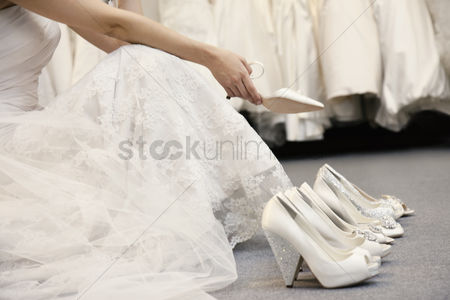 Variety : Low section of woman sitting with variety of footwear in bridal boutique
