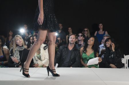 Show : Low section of womans walking in black high heeled shoes on fashion catwalk