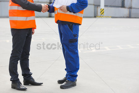 Supervisor : Low section of workers shaking hands in shipping yard