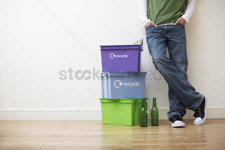 Symbol : Low section view of young man leaning against wall next to small pile of recyling containers