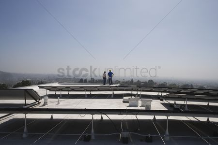 Land : Maintenance workers stand with solar array on rooftop in los angeles california
