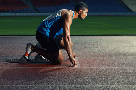 Sports : Male athlete crouching on starting line