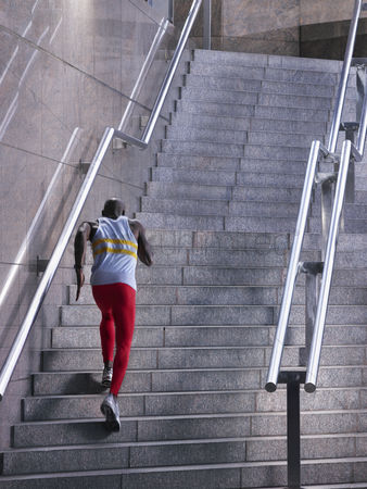 Sports : Male athlete running up staircase outside building