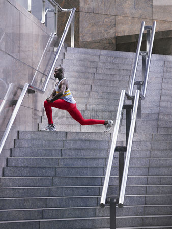 Staircase : Male athlete stretching on staircase outside building