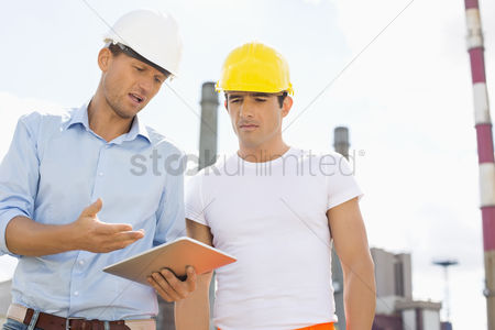 Supervisor : Male construction workers discussing over digital tablet at industry