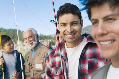 Masculinity : Male members of three generation family on fishing trip focus on mid adult man  portrait