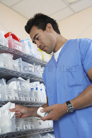 Choosing : Male nurse standing by shelves with medical supply low angle view