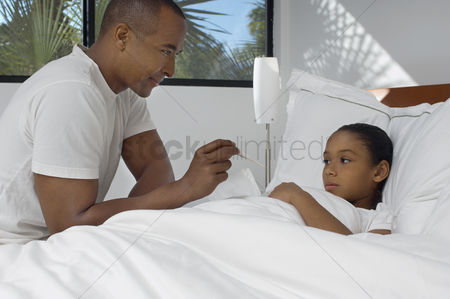 Thermometer : Male nurse taking temperature of girl  7-9  lying in bed