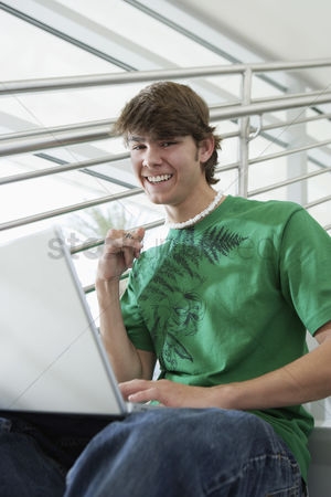 Pupil : Male student using laptop on stairs portrait