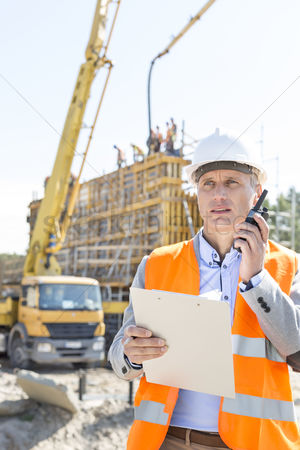 Supervisor : Male supervisor using walkie-talkie while holding clipboard at construction site