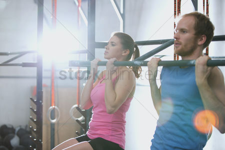Three quarter length : Man and woman doing pull ups in crossfit gym