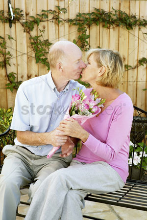 Kissing : Man and woman kissing while holding a bouquet of flowers