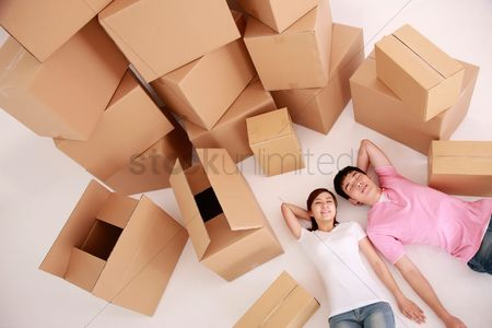 Three quarter length : Man and woman lying down with moving boxes next to them