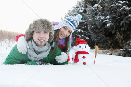 Lying forward : Man and woman posing with snowman