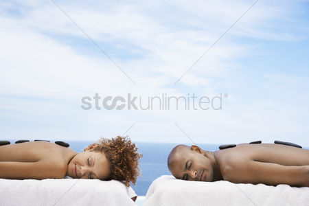 Curly hair : Man and woman receiving hot stone therapy at spa ocean behind