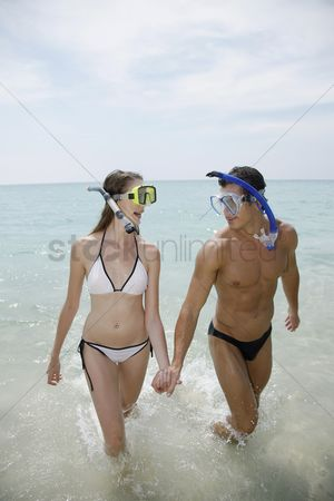 Diving : Man and woman with snorkeling gear on beach
