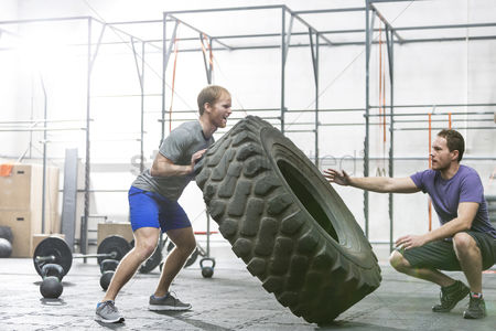 Strong : Man assisting at dedicated friend in flipping tire at crossfit gym