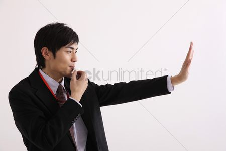 Blowing : Man blowing whistle and making a stop gesture