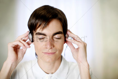 Satisfying : Man closing his eyes while listening to music on the headphones