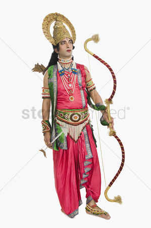God : Man dressed-up as rama and holding a bow and arrow