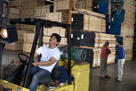 Forklift : Man driving forklift in warehouse of wood