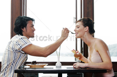 Lover : Man feeding his girlfriend at a restaurant