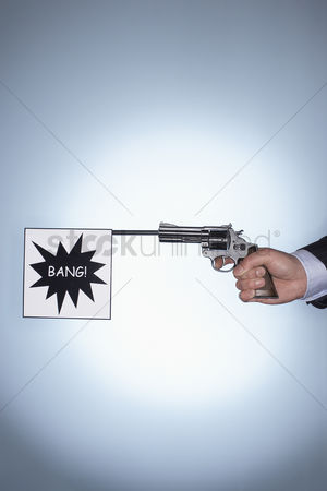Firing : Man firing pistol with bang flag close-up of hand