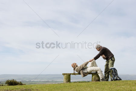 Couples : Man helping girlfriend up from a park bench