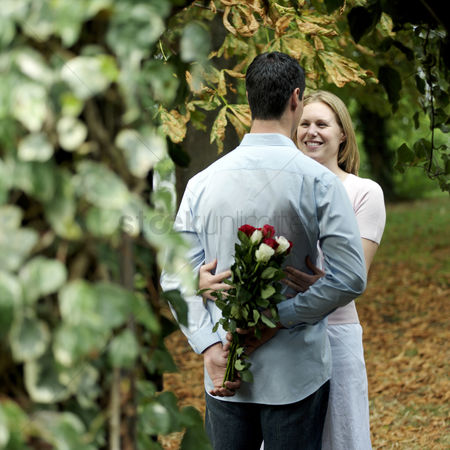 Outdoor : Man hiding a bouquet of flowers from his girlfriend