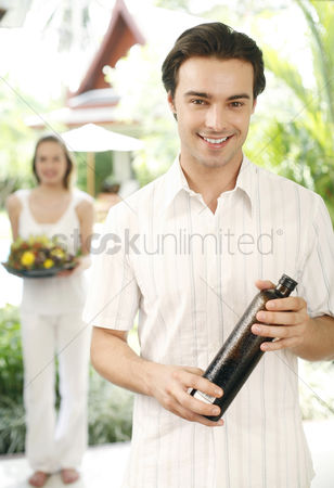 Wine bottle : Man holding a bottle of drink with his girlfriend holding a basket of flowers