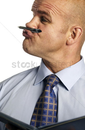 Bald : Man holding a pen in between his nose and lips